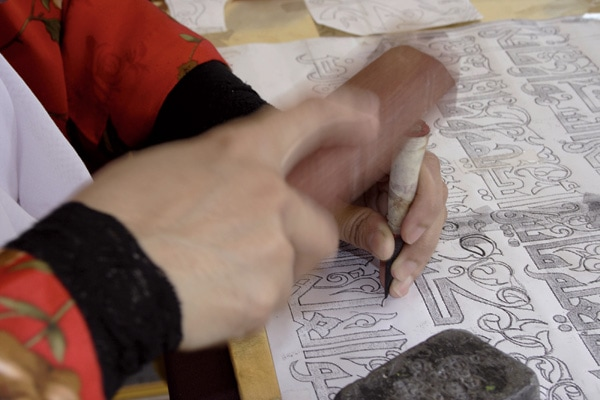 One of the initial steps of engraving copper with Arabic calligraphy is pounding the design out over a paper pattern